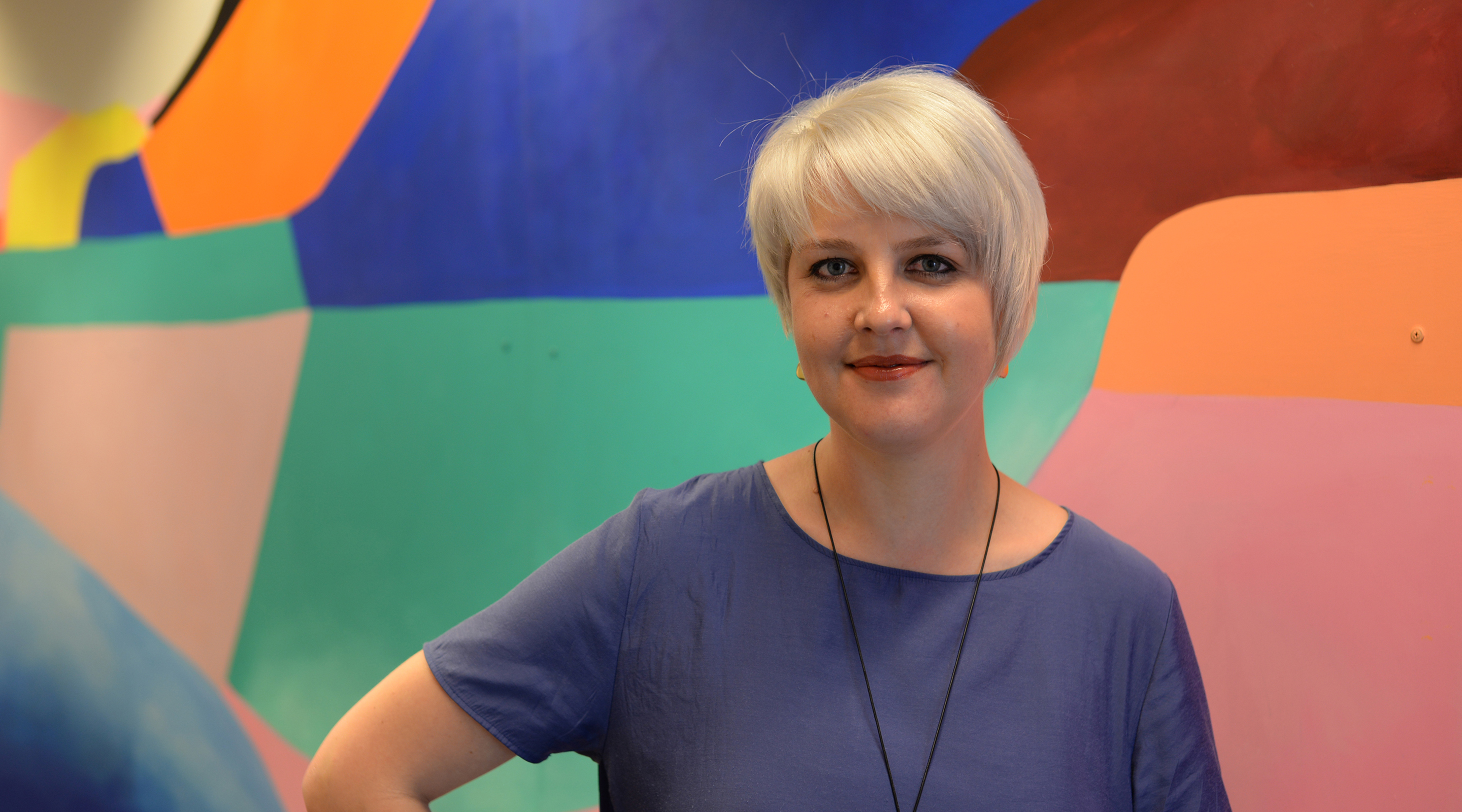 Dr Madeline Shanahan in front of a colourful wall